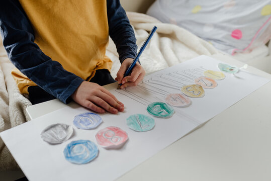 Anonymous child alone in the bedroom working on a mathematics lesson placing numbers in the correct order from 1 - 10 for remote school learning at home.