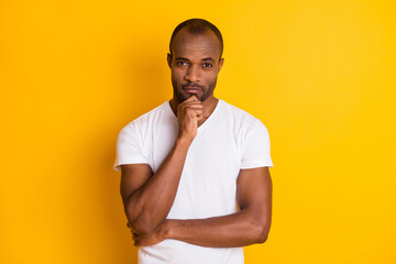 Photo of attractive dark skin guy hold arm on chin self-confident business man clever person wear casual white t-shirt blue jeans isolated bright vivid yellow color background