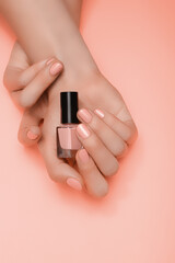Female hands with pink nail design. Pink nail polish manicured hands. Woman hands hold pink varnish...