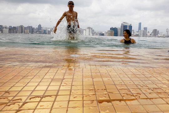 A boy jumps into the water next to his mother at the gold-plated infinity pool of the newly inaugurated Dolce Hanoi Golden Lake luxury hotel in Hanoi