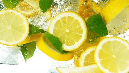 Lemon Slices falling deeply under water on white