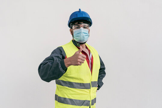 Construction worker portrait on white wall posing with face mask covid -19 prevention