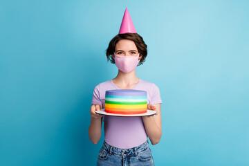 Portrait of positive cheerful girl in medical mask celebrate covid quarantine birthday hold cake...