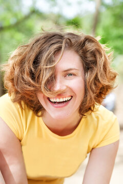 Vertical natural portrait of happy smiling curly 25 years old girl without make-up. Healthy skin. Summer happiness