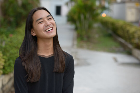 Happy young Asian man with long hair smiling at the park