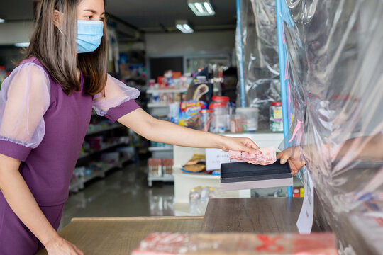 Asian customer wearing protective mask paying money at cashier counters in supermarket  with sneeze guard or plastic partition shields ,social distancing during covid-19 pandemic concept