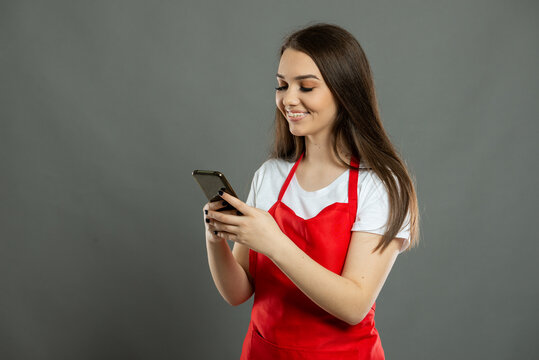 Portrait of young female supermarket employee texting on smartphone