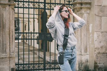 Brunette girl in glasses and a gray sweatshirt on the street near a black gate. On her shoulder Leather Utility Belt Pouch, Utility Belt, Cell Phone Crossbody Purse. Selective focus.
