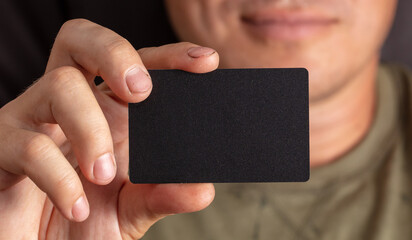 Close up of a black plastic card in a hand.