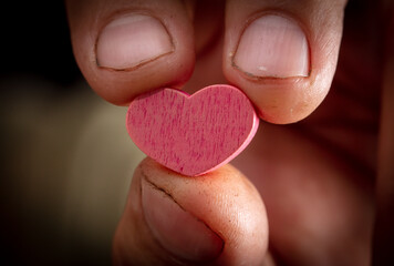 Close up of a pink heart in a hand.