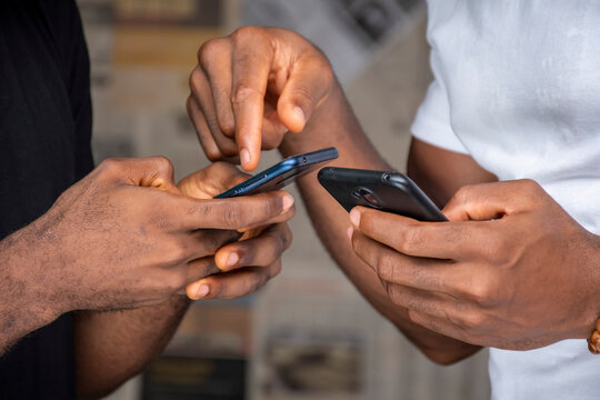 two young african people people using their mobile phones, transferring media