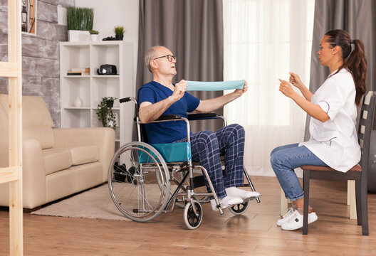 Senior man with disability in wheelchair doing recovery exercise with resistance band. Disabled handicapped old person with social worker in recovery support therapy physiotherapy healthcare system