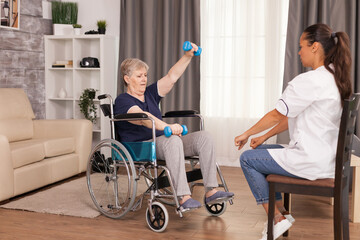 Invalid senior woman using weights with the help of nurse. Disabled handicapped old person...
