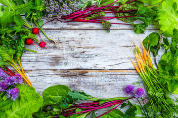 Frame with raw seasonal vegetables from garden on a wooden background. Vegetarian food with space for text.