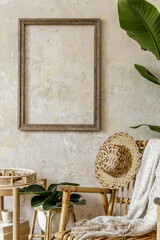 Stylish and beige composition of home interior with rattan armchair, mock up poster frame, coffee...