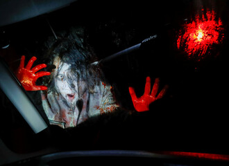 An actor dressed as a zombie performs during a drive-in haunted house show by Kowagarasetai, for people inside a car in order to maintain social distancing amid the spread of the coronavirus disease (COVID-19), in Tokyo