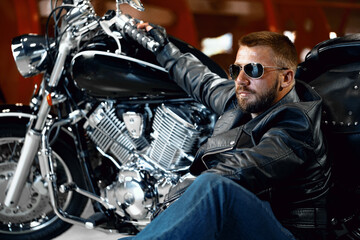Cool man biker in sunglasses sitting near his motocycle