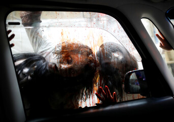 Actors dressed as zombies or ghouls perform during a drive-in haunted house show by Kowagarasetai, for people inside a car in order to maintain social distancing amid the spread of the coronavirus disease (COVID-19), in Tokyo