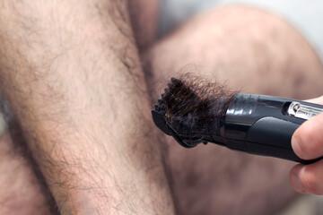 Dłoń mężczyzny trzyma maszynkę elektryczną do strzyżenia włosów i obcina długie ciemne włosy na swoich nogach.
