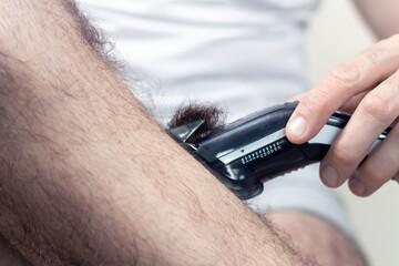 Mężczyzna trzyma w dłoni maszynkę do strzyżenia i obcina włosy na łydce.