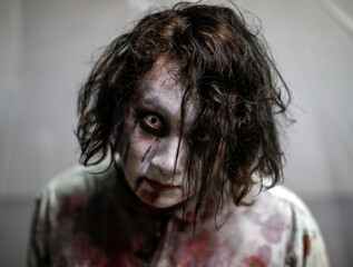 An actor dressed as a zombie is seen before their performance at a drive-in haunted house show by Kowagarasetai, in Tokyo