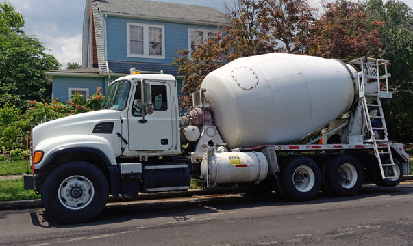 Concrete mixer truck parked on residential neighborhood street.