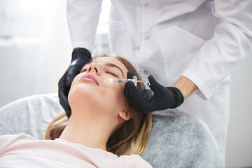 Beautician doctor injects hyaluronic acid on the lips of a young beautiful woman in a beauty salon....