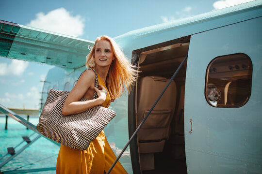 Portrait of young woman boarding airplane