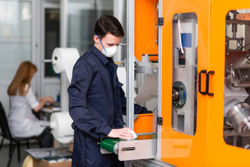 A man works at a machine for the manufacture of medical masks with nanofiber. Coronovirus and Covid-19 Prevention