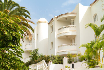 White beautiful house with exotic garden. Vibrant palm trees and blue sky. Tenerife, Spain
