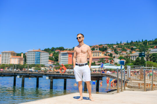 Man with muscular body and strong torso in sunglasses at the sea