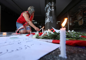 A woman lights a candle at the site where a man killed himself in Beirut