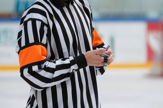 An ice hockey referee making notes on a small notebook during a game break.