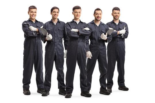 Team of five auto mechanic workers in uniforms