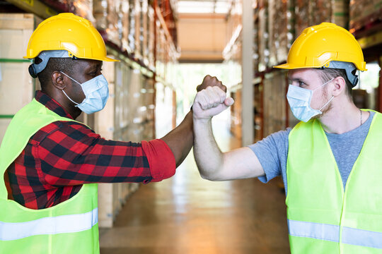 Elbow greeting to avoid the spread of coronavirus (COVID-19). African and caucasian worker man wear face mask greeting with elbow bump at warehouse. Employee avoid touch for coronavirus prevention.