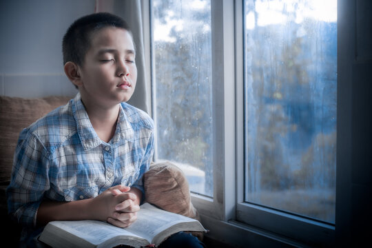 Boy praying and Seek God with the holy Bible in morning at home. Children's beliefs of christian concept.