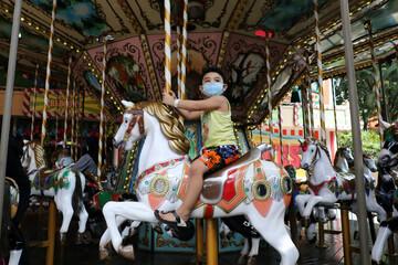 A boy wearing a protective mask enjoys a theme park ride at Sunway Lagoon, as theme parks reopen amid the coronavirus disease (COVID-19) outbreak, in Subang Jaya
