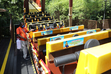 A worker sprays disinfactant on a theme park ride at Sunway Lagoon, as theme parks reopen amid the coronavirus disease (COVID-19) outbreak, in Subang Jaya