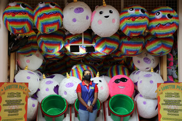 A worker wearing a protective mask waits for customers at a fun fair booth at Sunway Lagoon, as theme parks reopen amid the coronavirus disease (COVID-19) outbreak, in Subang Jaya