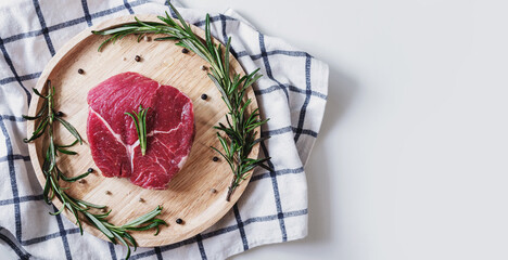 Raw meat, beef steak, on wooden board with rosemary