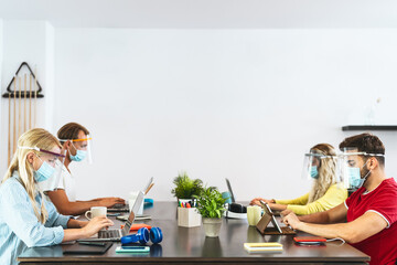 Young people working in co-working creative space wearing surgical mask protection for preventing...