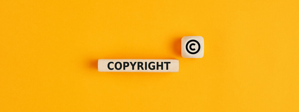 The word copyright and copyright symbol on wooden blocks. Concept of patenting. or copyright protection.