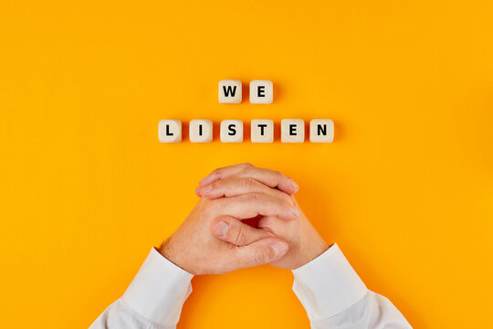 We listen words written on wooden blocks and hands of a businessman on yellow background