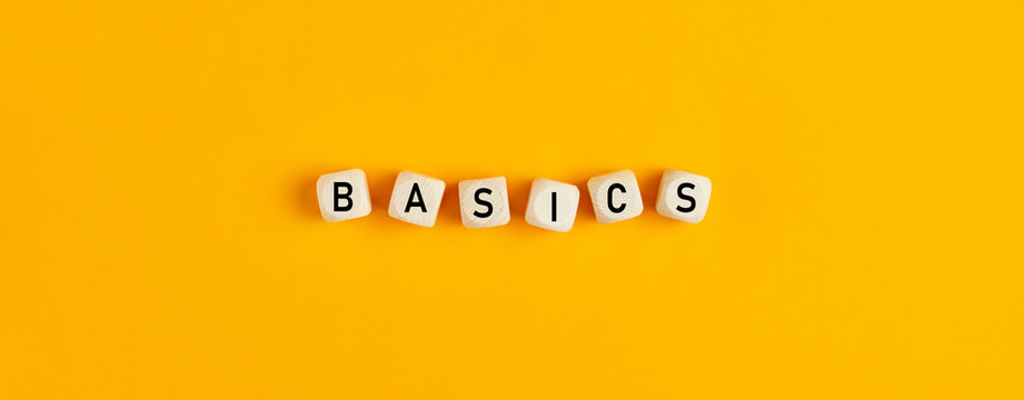 Basics word written on wood blocks on yellow background with flat lay view
