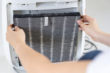 Asian woman changing the dirty air purifier filter after using for a long time in the dirty air environment. Using air purifier clean the air for better atmosphere in a house.