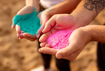 Crop people with colorful powder on beach