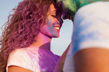 Happy couple touching foreheads during paint holiday