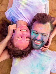 Young couple resting on beach during paint party