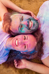 Couple smiling and lying on beach during paint holiday