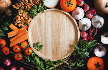 Wooden dish surrounding with fresh organic food ingredient, vegetables, herb and spices, on black background